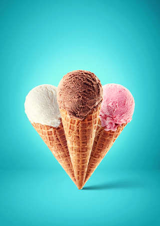 Chocolate, strawberry and vanilla ice cream with cone on blue background. Three different flavors Foto de archivo