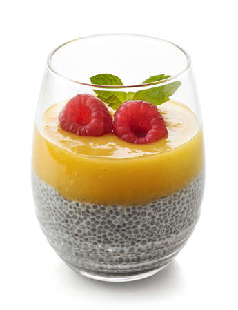 Healthy vegan chia pudding with mango sauce and fresh raspberries isolated on white background