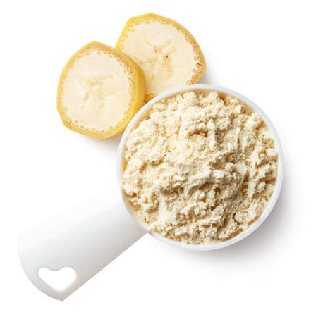Plastic measuring spoon of yellow banana protein powder isolated on white background. Top view