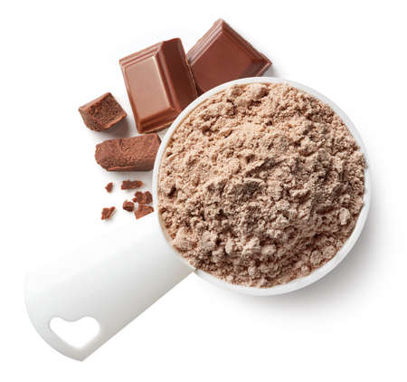 Plastic measuring spoon of brown chocolate protein powder isolated on white background. Top view Stock Photo