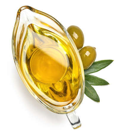 Glass gravy boat of fresh extra virgin olive oil isolated on white background. Top view