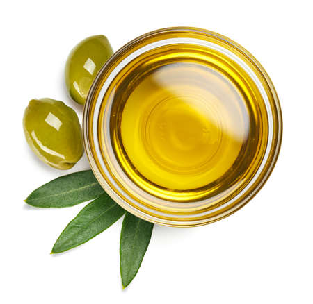 Bowl of fresh extra virgin olive oil and green olives with leaves isolated on white background. Top view 免版税图像 - 105692451