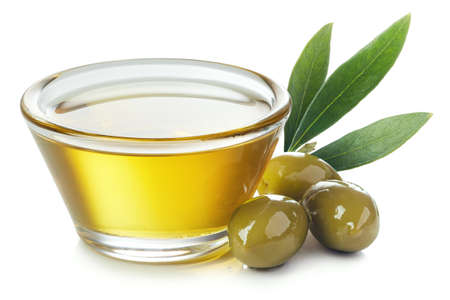 Glass bowl of fresh extra virgin olive oil and green olives with leaves isolated on white background