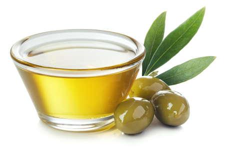 Szklana miska świeżej oliwy z oliwek extra virgin i zielonych oliwek z liśćmi na białym tle