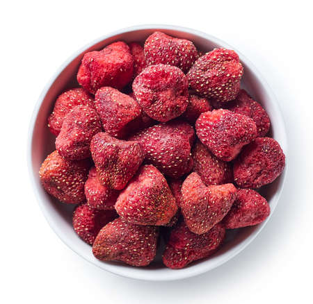 Bowl of freeze dried strawberries isolated on white background. Top view