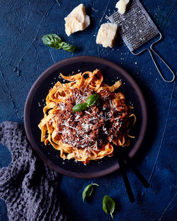 Italian pasta Bolognese with basil and Parmesan cheese on blue