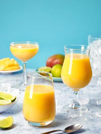 Three glasses of fresh healthy mango smoothies on blue background