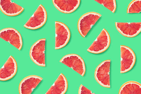 Colorful fruit pattern of grapefruit slices on green background. Top view. Flat lay Stock Photo