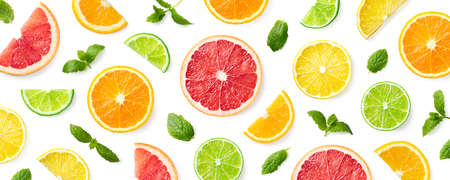 Colorful pattern of citrus fruit slices and mint leaves isolated on white