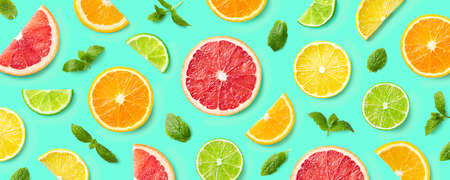 Colorful pattern of citrus fruit slices and mint leaves on blue