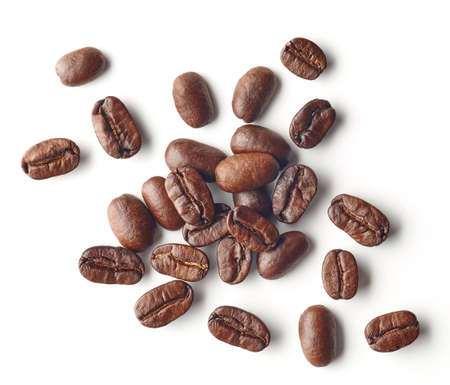 Montón de granos de café tostados aislado sobre fondo blanco, vista superior