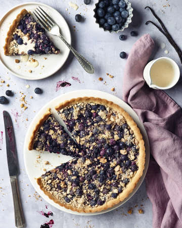 Blueberry pie with vanilla sauce and fresh berries on gray marble background