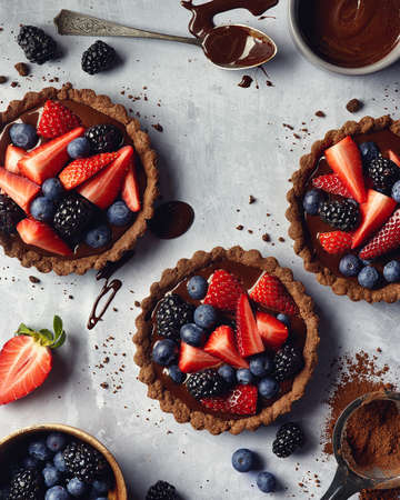 Chocolate tarts with fresh berries on gray marble background