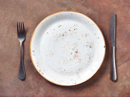 Empty plate with fork and knife on brown grunge concrete background. Top view
