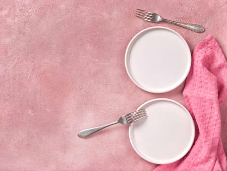 Two empty dessert plates, forks and napkin on pink concrete background. Top view, space for text