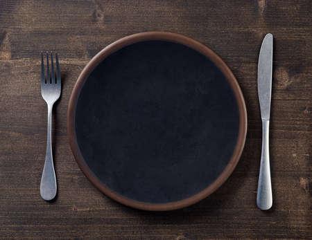 Schwarzer leerer Teller und Besteck auf dunklem Holzhintergrund, Ansicht von oben