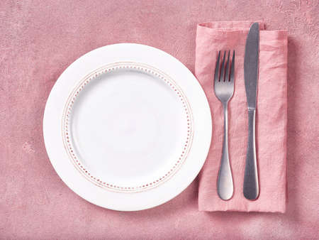 White empty plate, cutlery and napkin on pink concrete background. Top view