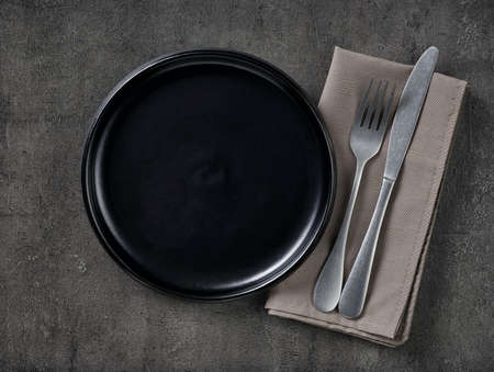 Black empty plate, cutlery and napkin on gray concrete background. Top view