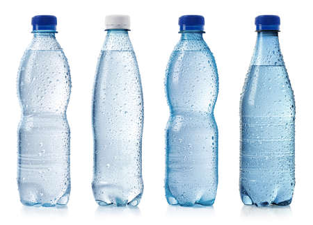 Collection of various cold bottles of water with drops isolated on white background