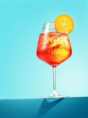 Glass of spritzer cocktail on blue background