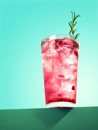 Glass of pomegranate spritzer cocktail with rosemary on green background Banco de Imagens