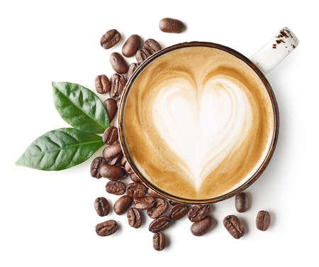 Taza de café con leche o arte capuchino con dibujo en forma de corazón y frijoles aislados sobre fondo blanco. Foto de archivo
