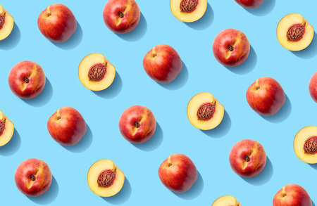 Colorful fruit pattern of fresh nectarines on  blue pastel