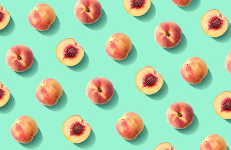 Colorful fruit pattern of fresh peaches on green pastel