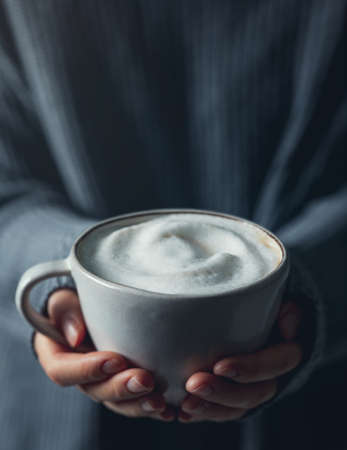 Woman hands holding a cup of hot chocolate topped with whipped cream and cinnamon stick