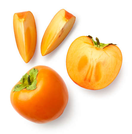 Fresh whole, half and sliced persimmon fruit isolated on white background, top view