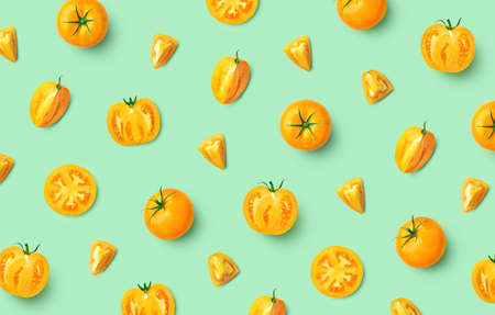 Colorful pattern of fresh whole and sliced yellow tomatoes, top view, flat lay