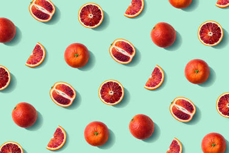 Colorful fruit pattern of fresh whole and sliced blood orange on mint background, top view, flat lay