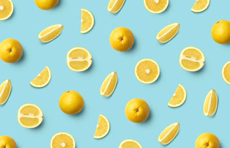 Colorful fruit pattern of fresh whole and sliced white grapefruit on blue background, top view, flat lay