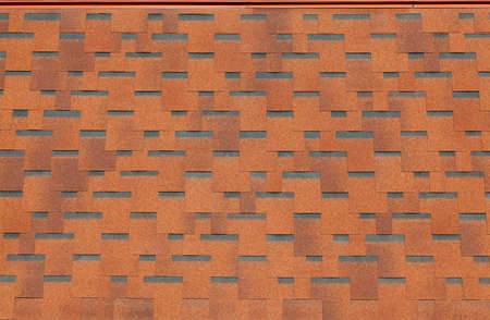 The texture of the roof with bituminous coating. Rough bituminous mosaic of red and brown flowers. Waterproof roofing. Stock Photo
