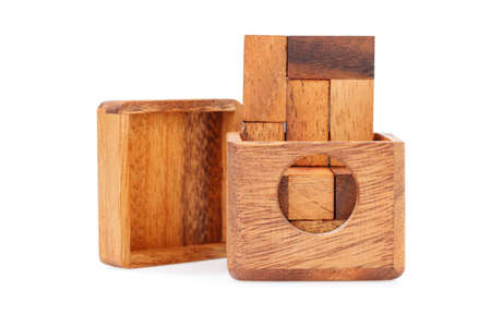 A wooden puzzle is a cube, logical game. Isolated on white background. Close-up. Imagens