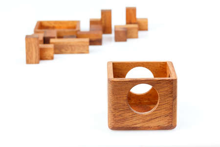 A wooden puzzle is a cube, logical game. Isolated on white background. Close-up. Stock Photo