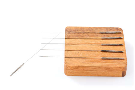Silver acupuncture needles, on a wooden stand, isolated on a white background. Close-up.