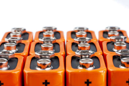 Many orange batteries, stand in several rows. Isolated on white background.
