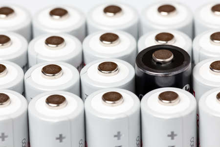 AA batteries are located close to each other. Close-up of all white batteries, except one black, on a white background. Battery technology. 스톡 콘텐츠