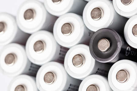 AA batteries are located close to each other. Close-up of all white batteries, except one black, on a white background. Battery technology. Stock fotó