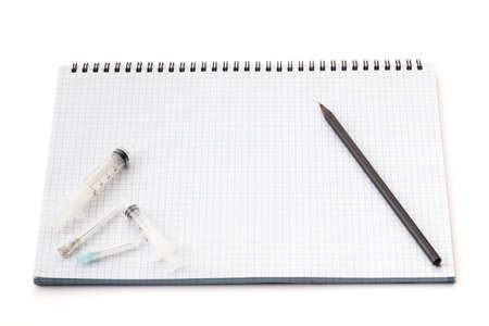 Needles for medical injections are on the notebook isolated on white background. There is free space for your text or sign.