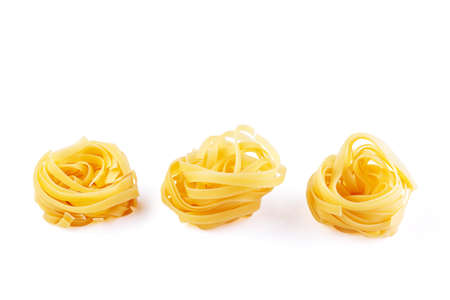 Italian rolled Raw noodles. Pasta isolated on white background. Egg homemade dry ribbon noodles, long rolled macaroni or uncooked spaghetti isolated.