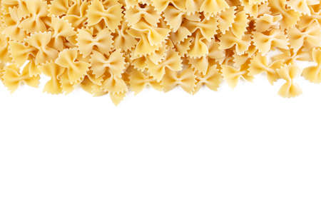 Variety of types and shapes of Italian pasta. Dry pasta background. A portion of Farfalle bows pasta isolated on white. Heap of bow tie pasta isolated on white background.