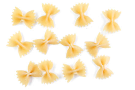 A variety of types and shapes of Italian pasta. Dry pasta bows farfalle. Heap of bow tie macaroni isolated on white background.