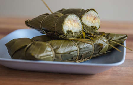 glutinous rice steamed in banana leaf on the blue plate on a wooden table  photo