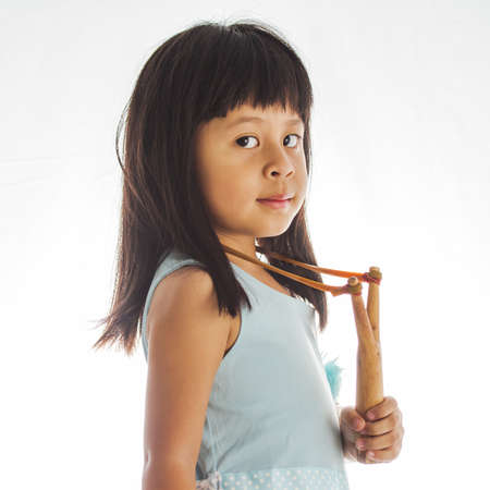 mischevious: little girl with a slingshot on white