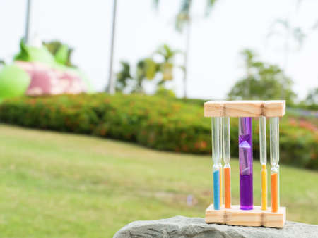 Hourglass on stone and blurred garden background,