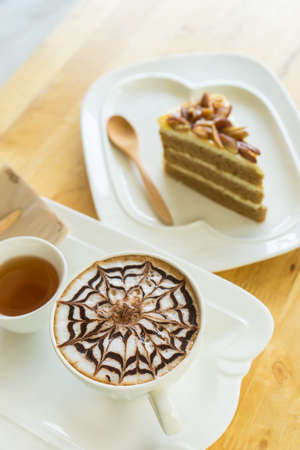 hot coffee late in white glass on wooden table, blurred cake and wooden spoon,