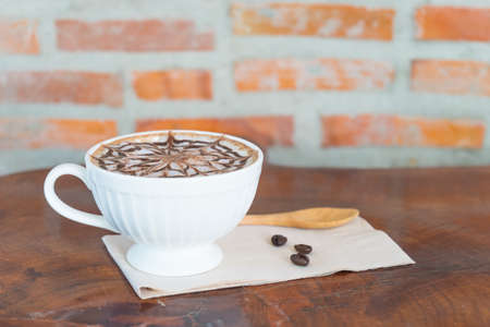 hot coffee late in white glass on wooden table, blurred raw coffee,