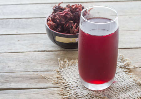 Roselle juice on wooden background, roselle juice in glass on sack,